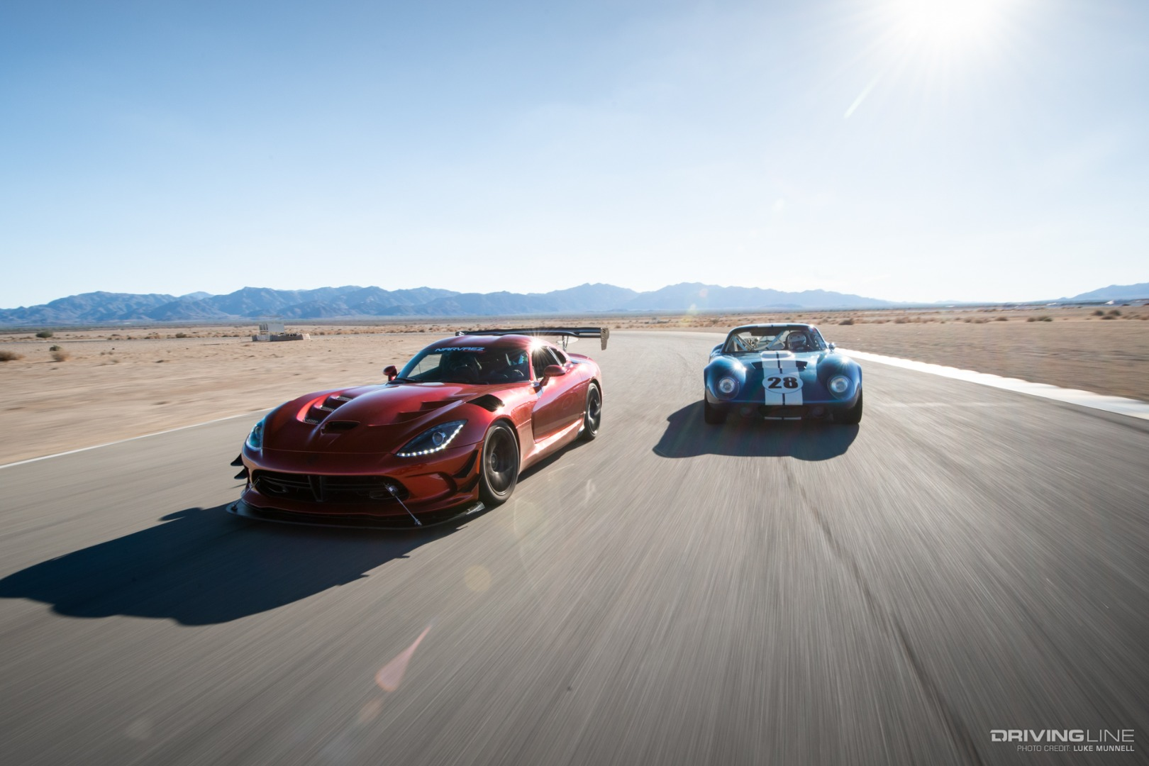 Orange Viper and Blue Shelby Cobra racing on a track
