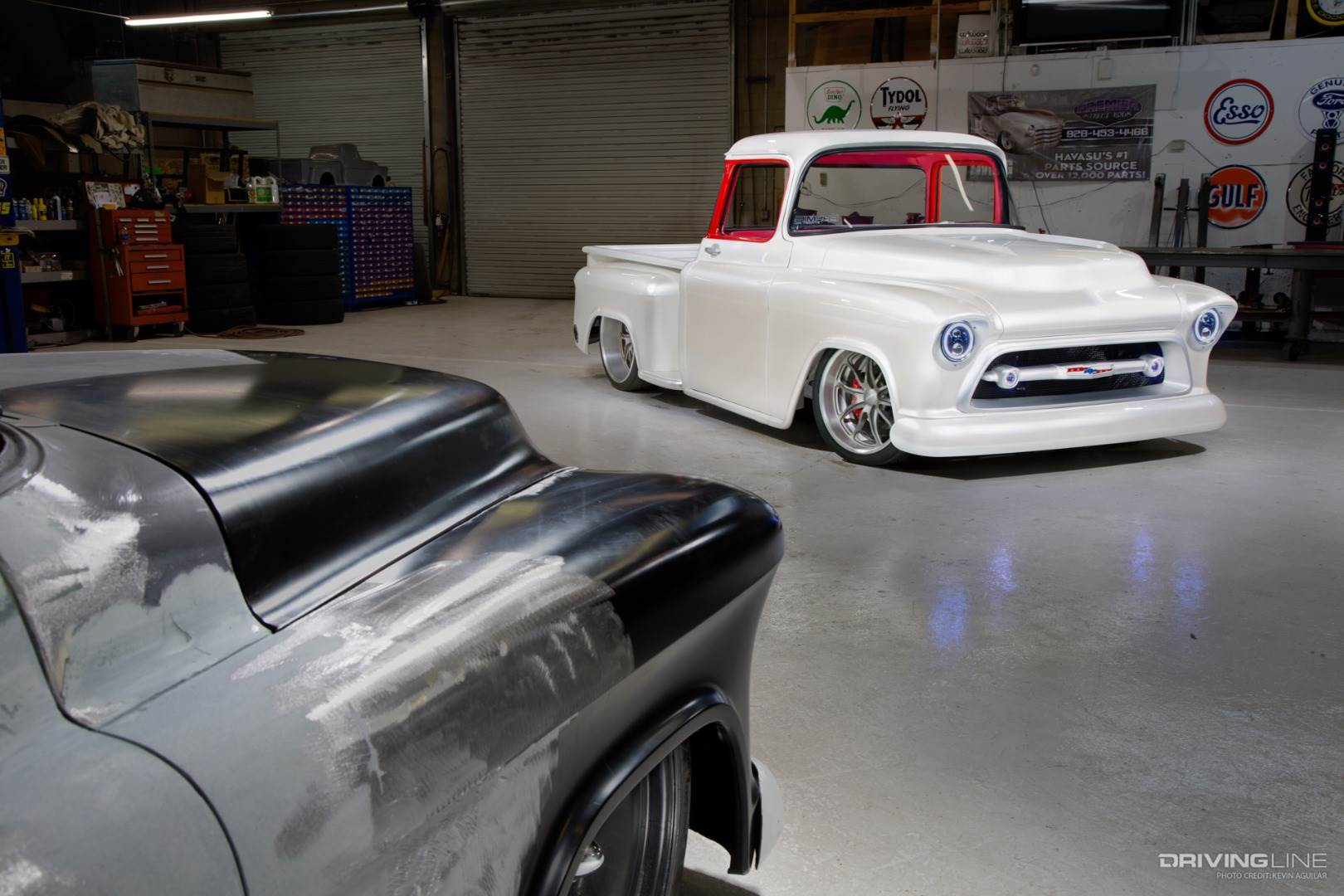 White lowered truck next to silver truck